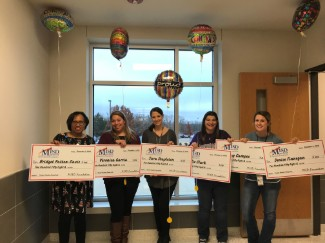 5 teachers holding oversized checks